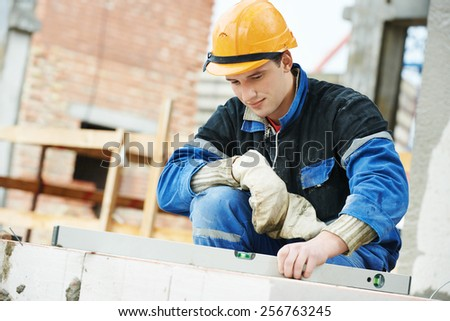 construction mason worker bricklayer working level levelling bricks - stock photo