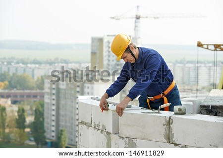 construction mason worker bricklayer working with limestone brick and measuring tape outdoors - stock photo