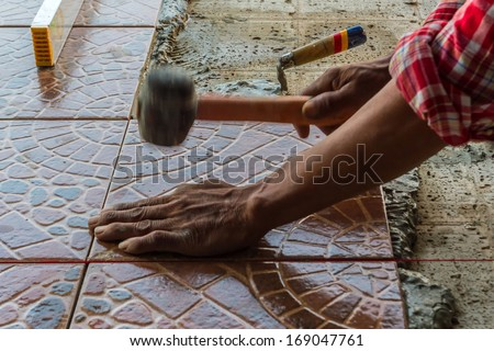 Construction mason worker floor tile installation. Home improvement. - stock photo