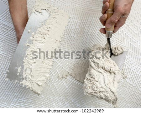 construction notched trowel and worker hands on big tile back side - stock photo