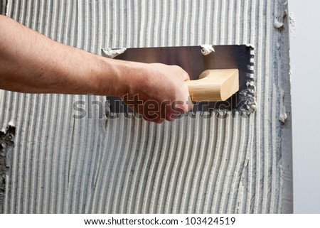 construction notched trowel with white cement mortar for tiles work