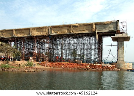 Construction of a bridge over the river - stock photo
