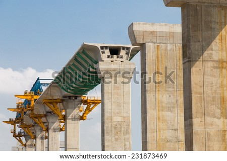 Construction of a mass transit train line in progress with heavy infrastructure.  This photo shows the progress in joining the various blocks/modules of the line with heavy equipment. - stock photo