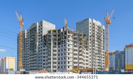 Construction of a new multi-storey panel house. Three tower cranes - stock photo