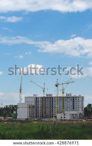 Construction of a new residential building in the field. City absorbs nature. Construction of suburban high-rise buildings
