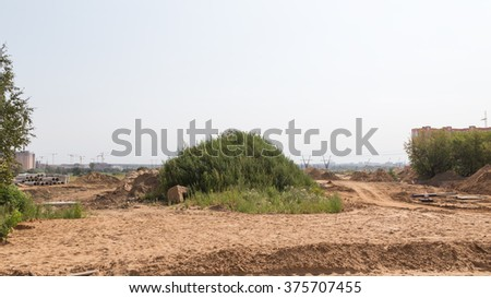 Construction of a new road in the new residential area, a lot of yellow sand and a large green hill with wild grass, Moscow Oblast Russia  - stock photo
