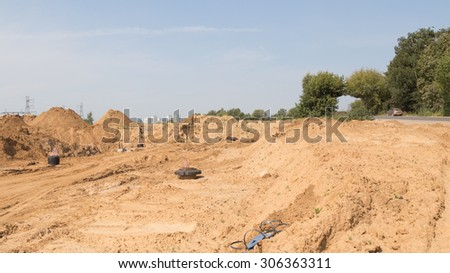 construction of a new road with light yellow sand fines on the construction site and the old road with an arch of trees goes close