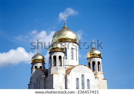 Construction of a new temple with gold domes against blue sky with light white clouds