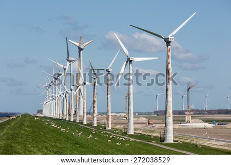 Construction of a new windfarm along the Dutch coast with the old existing smaller windturbines still in production - stock photo