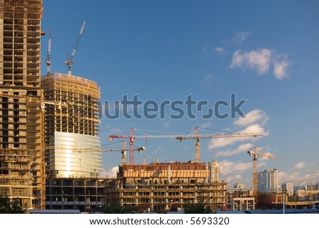 Construction of a skyscraper in Moscow, early morning. Many cranes. - stock photo