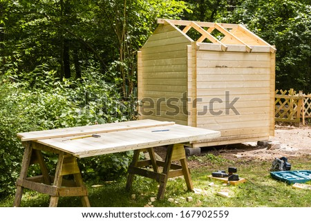 Construction of a wooden hut in a garden - stock photo
