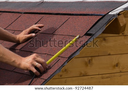 Construction of asphalt shingles on a roof of wood - stock photo