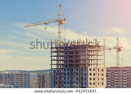 Construction of buildings with construction cranes at sunset.