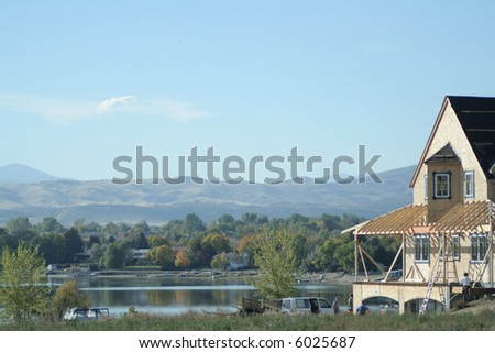 construction of luxury home in affluent neighborhood on a lake - stock photo