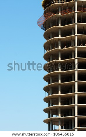 Construction of modern building against blue sky - stock photo