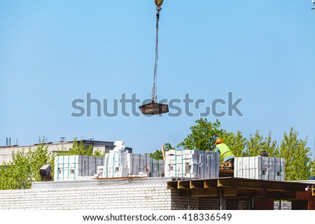 Construction of multi-storey brick building. A crane lowers the load against the blue sky  - stock photo