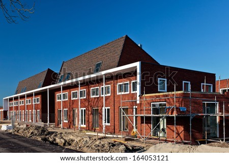 Construction of nearly finished Dutch family houses, build in a row - stock photo