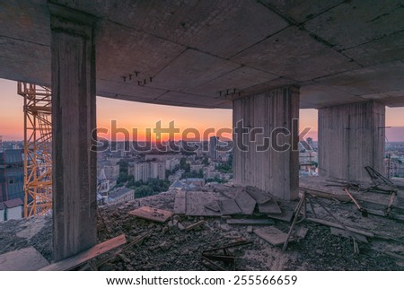 Construction of office building on purple sunset with tower crane, view from the top floor to the big city - stock photo