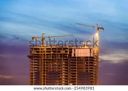 Construction of office building on purple sunset with two tower cranes - stock photo