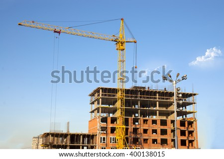 construction of residential brick house with gantry crane - stock photo