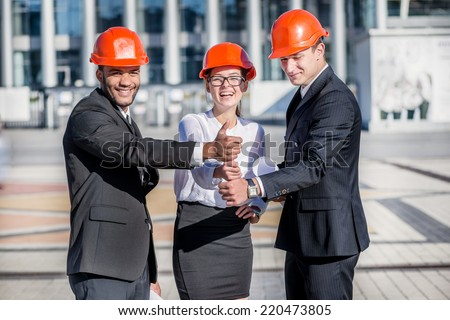 Construction of the best architects. Three confident business architect in protective helmet standing on construction site and holding blueprints in hand and show a thumbs up - stock photo