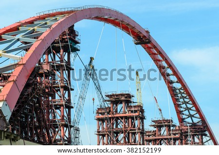 Construction of the bridge across the river. - stock photo