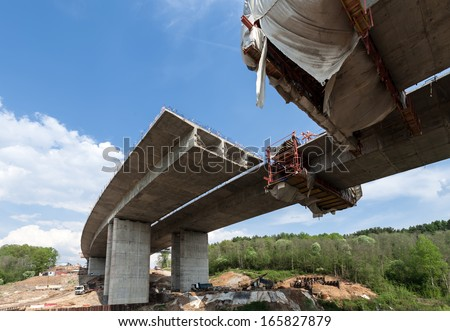 Construction of the bridge by the prestressed concrete method - stock photo