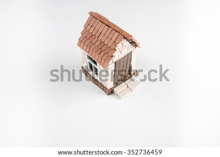 Construction of toy brick house in progress. White background. Top perspective view. - stock photo