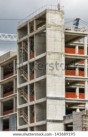 Construction on a large commercial building showcases a stairwell with temporary railings and bright orange safety fences along the building perimeter. - stock photo
