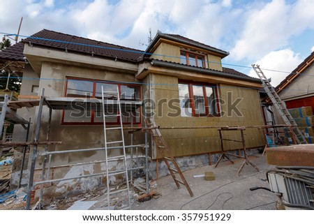 Construction or repair of the rural house, fixing facade, insulation and using color for new look - stock photo