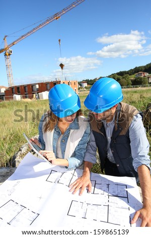 Construction people looking at blueprint - stock photo