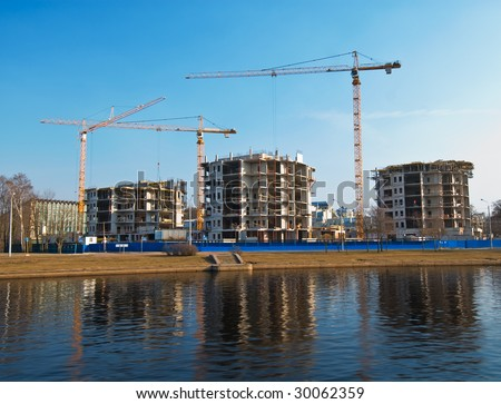 Construction place at the river front with reflection - stock photo