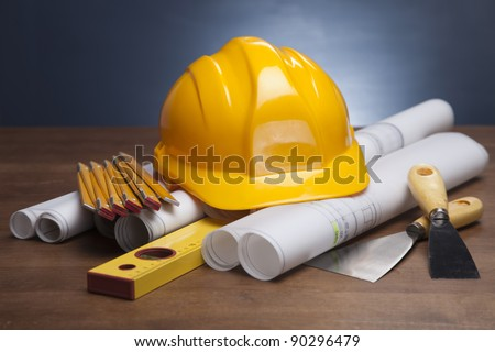 Construction plans and blueprints on wooden table - stock photo