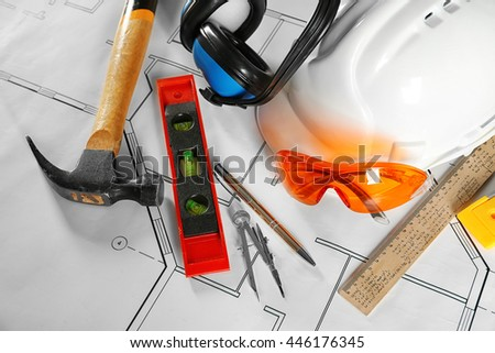 Construction plans and builder equipment on table - stock photo