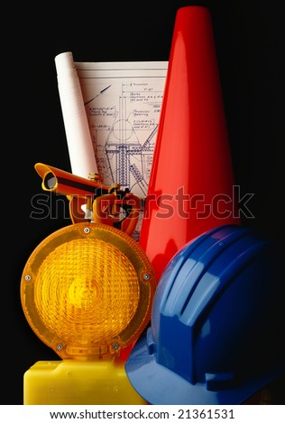 Construction plans with warning light, cone and surveyor's transit - stock photo