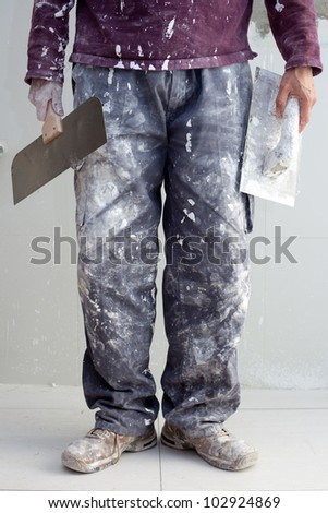 construction plastering man dirty trousers with trowel in hand - stock photo