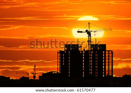 Construction project silhouette against sunset sky with big sun setting down - stock photo