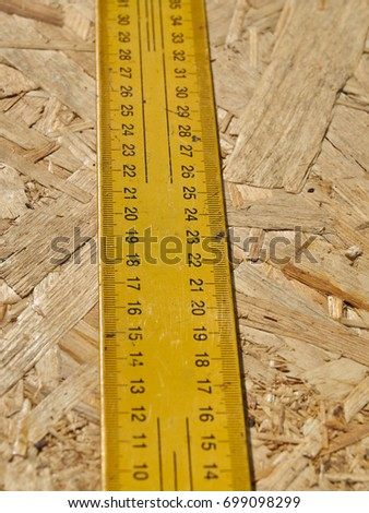 Construction ruler on a wooden background