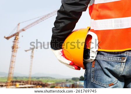 Construction safety concept, close-up worker holding hardhat with crane in the background - stock photo