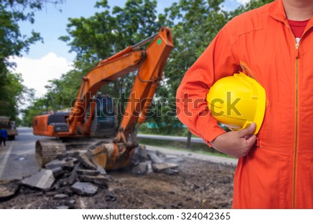 Construction safety concept, close-up worker wearing safety vest holding helmet with site background - stock photo