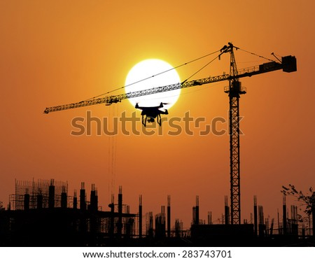 Construction Site and drone silhouette in the sunset background - stock photo