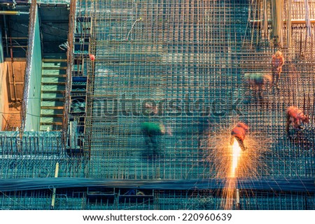 Construction site at night with workers who weld - stock photo