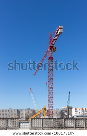 construction site behind a fence with a high crane - stock photo