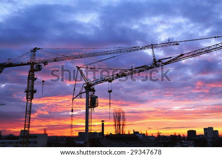 Construction site - cranes at dramatic dawn - stock photo