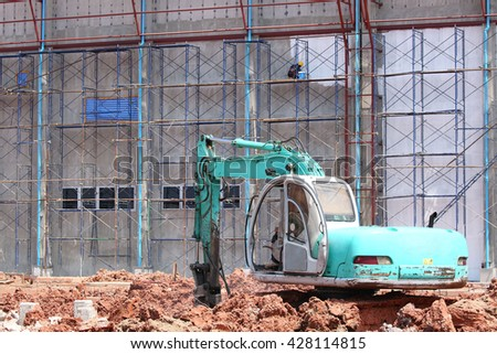 Construction site, excavator breaking and drilling the concrete - stock photo