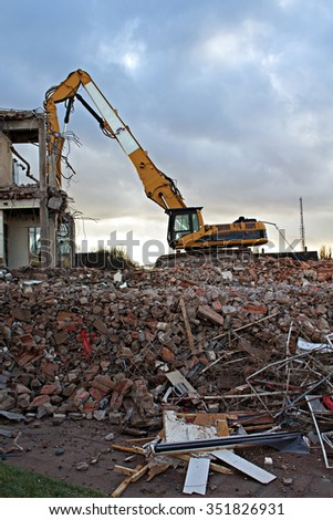 Construction Site Excavator Dismantling a Building - stock photo