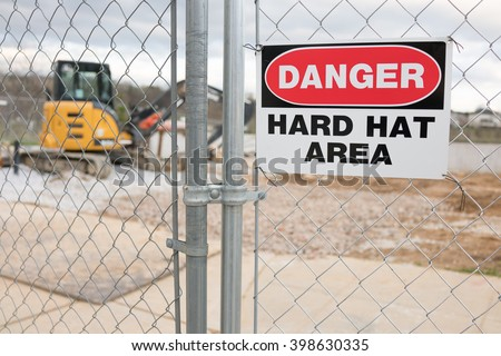 Construction Site Fence With Danger Hard Hat Area Warning - stock photo