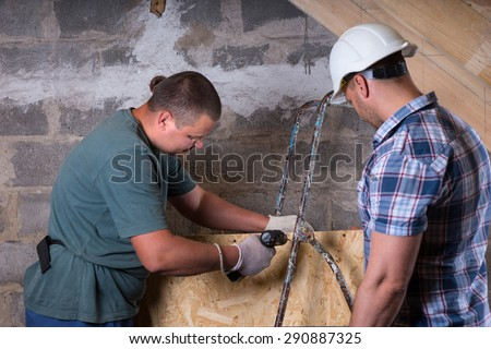 Construction Site Foreman Wearing White Hard Hat Monitoring Worker Using Power Tool Drill in Unfinished Basement of New Home - stock photo