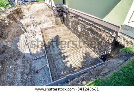 construction site foundation. There is a construction site underneath the house. The construction hole is full of construction iron and steel and gravel. Building extension to a family house - stock photo