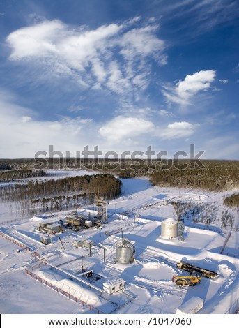 Construction site in wild winter forest. Building of petrochemical plant - stock photo